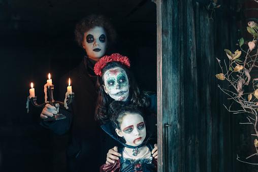 three kids in spooky halloween costumes hiding behind door of old barn