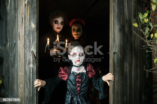three kids in spooky halloween costumes hiding behind door of old barn