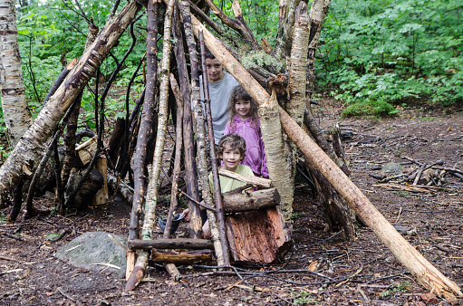 Three kids in the wooden shelter