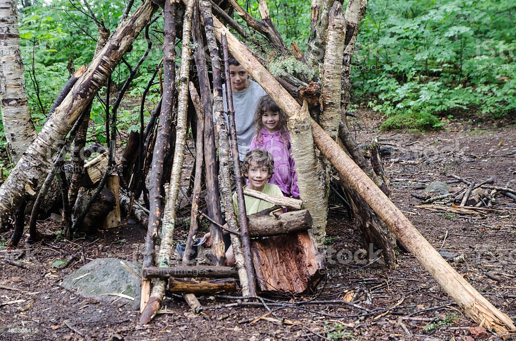 Three kids in the wooden shelter stock photo