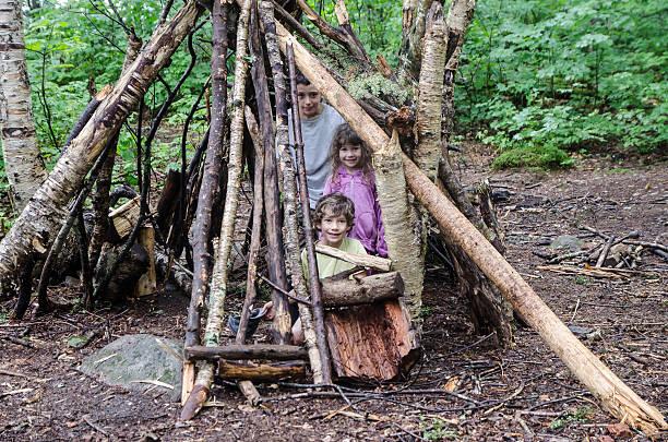 drei kinder im holz-shelter - mädchen spielhaus stock-fotos und bilder