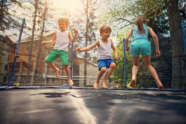 tres niños saltando en trampolín grande - trampolín artículos deportivos fotografías e imágenes de stock