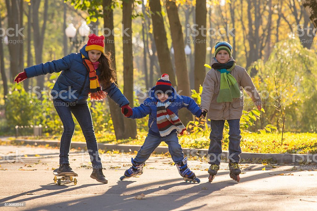 Three kids learning to ride in autumn park on rollerblades - foto de acervo