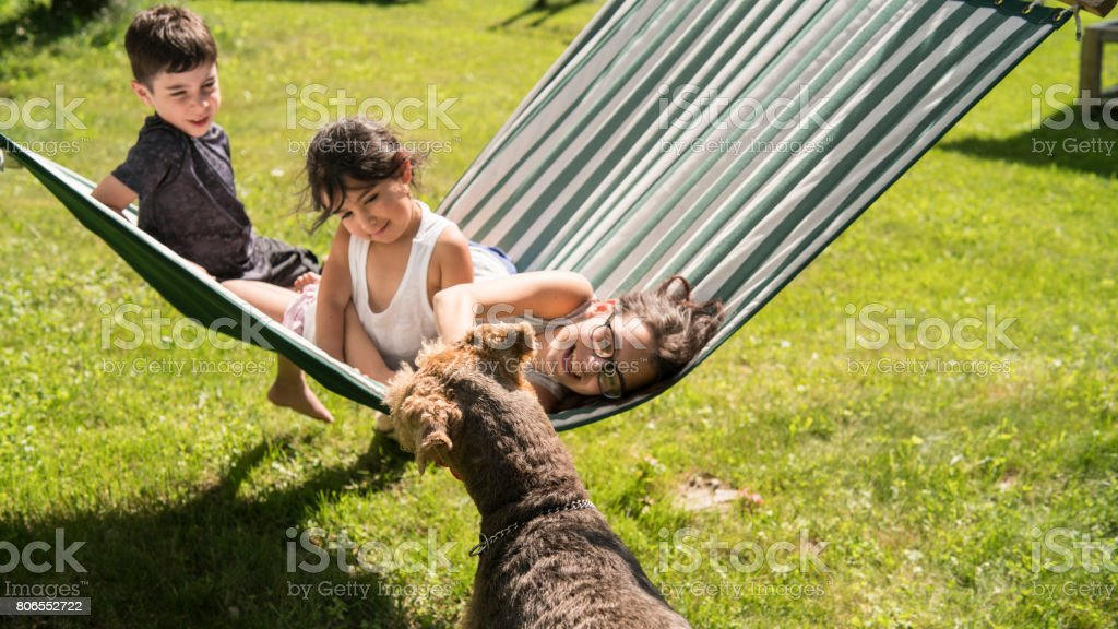 Three kids, little girl, little boy and teenager girl, brother and sisters, playing in the hammock stock photo