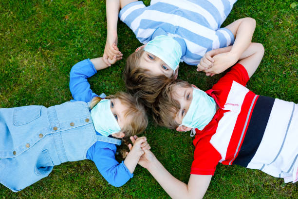 three kids, little toddler girl and two kid boys in medical mask as protection against pandemic coronavirus disease. Children, lovely siblings using protective equipment as fight against covid 19. stock photo