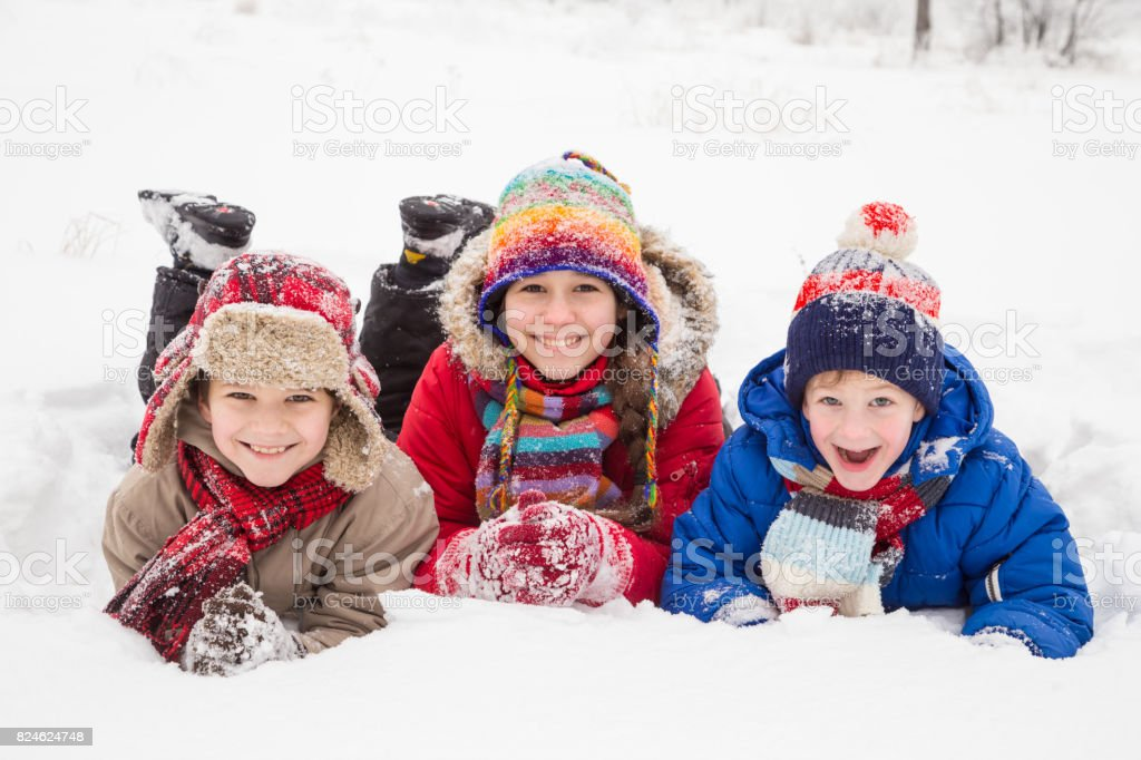 Three kids lying down together on winter snow stock photo