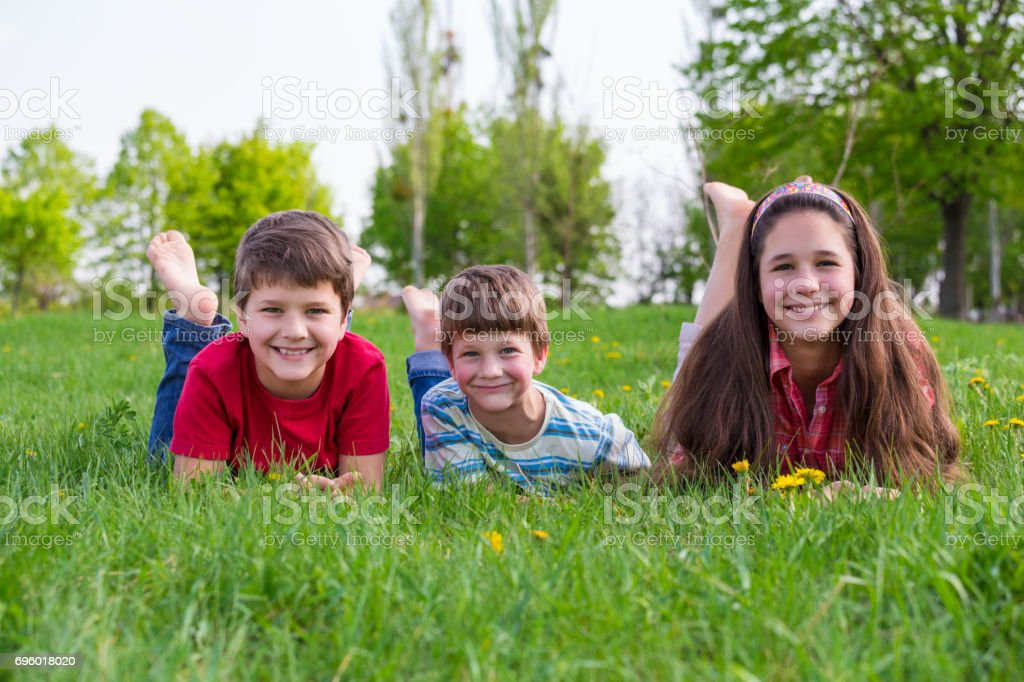 Three kids lying together on green grass meadow stock photo