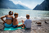 Brothers and sister having fun in Riva del Garda on the shore of Lake Garda, Italy. Kids aged 9 and 13 are enjoying the beach and meeting  wild duck and pigeon.\nNikon D850