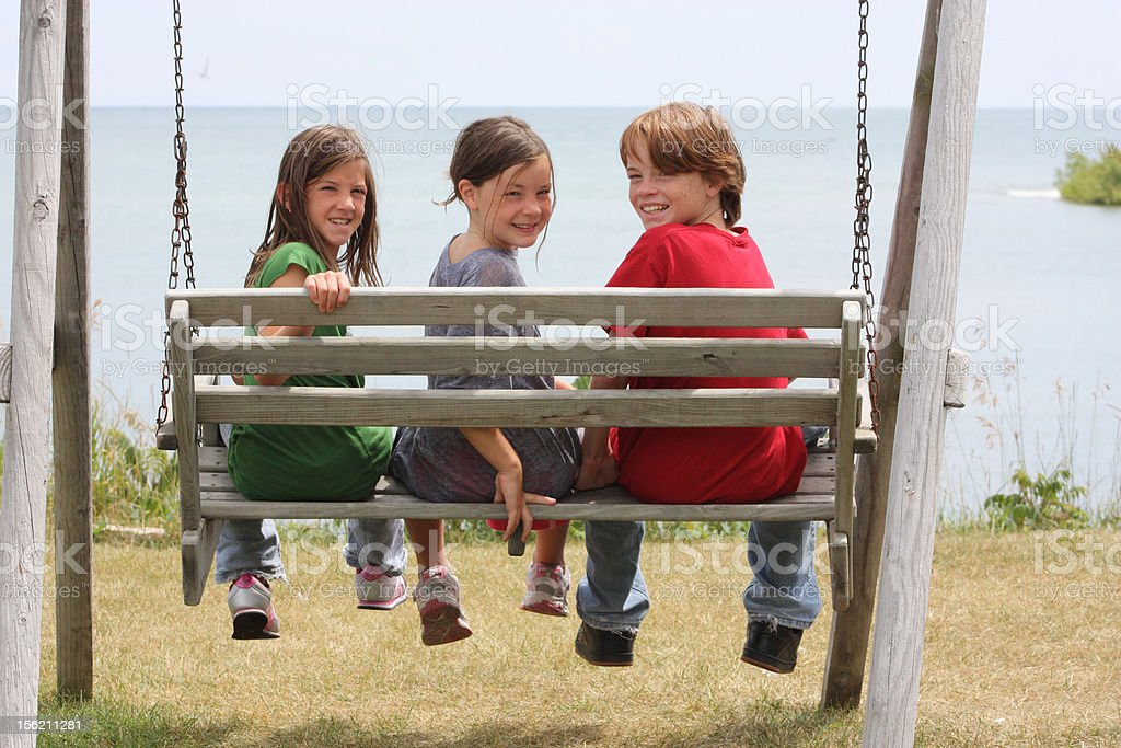 Three kids on swing at lake royalty-free stock photo