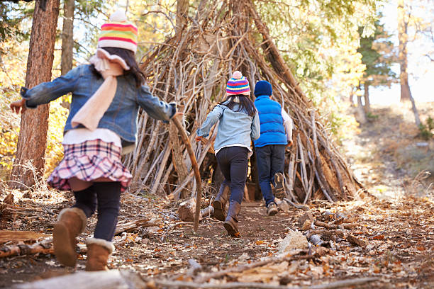 Three kids play outside shelter made of branches in stock photo