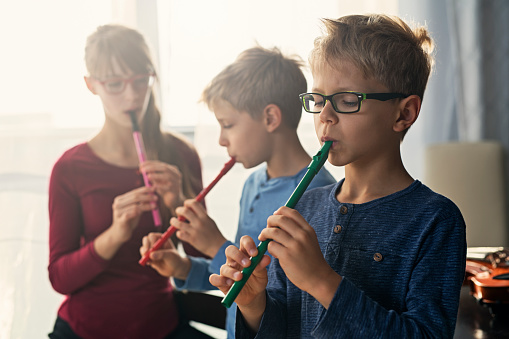 istock Three kids playing flutes together 1048477090