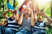 Three kids lying on hammock on sunny spring day. They are playing with Easter eggs.\nNikon D850