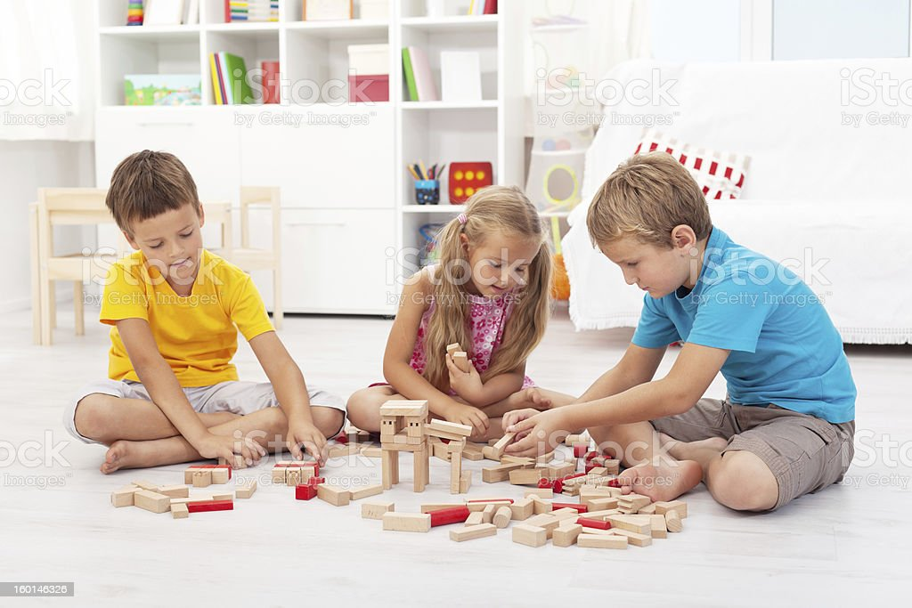 Three kids playing with wooden blocks royalty-free stock photo
