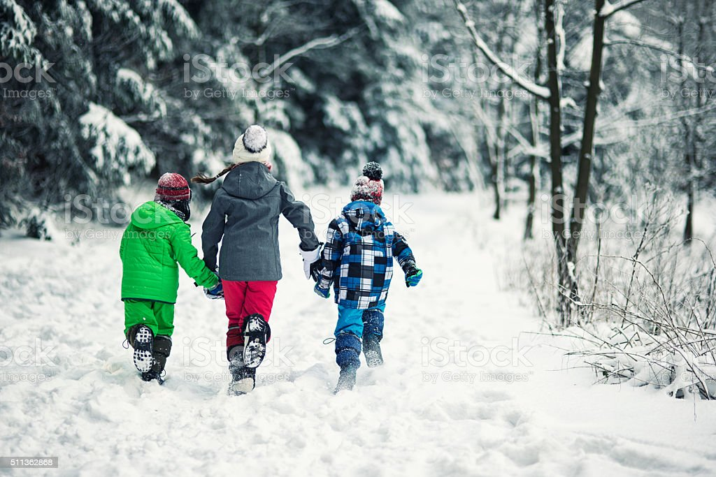 Three kids running in winter forest stock photo