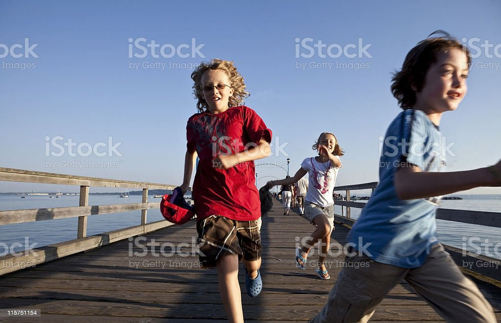 Three kids Running On Pier late in the day. royalty-free stock photo