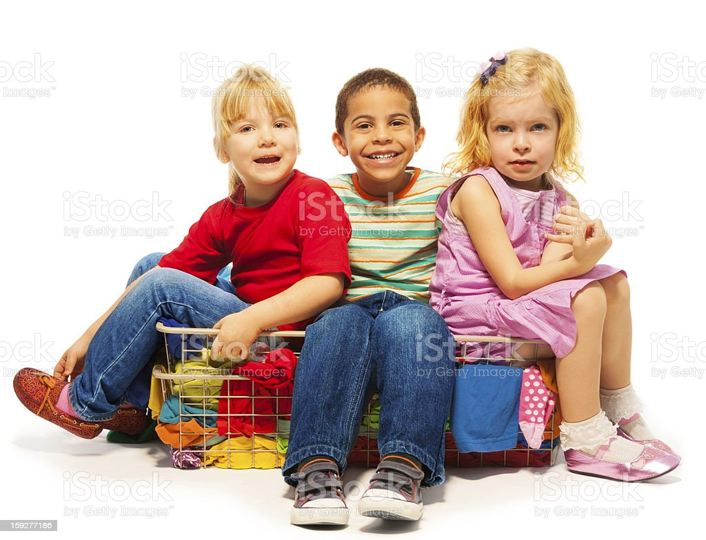three kids sitting in the clothes basket royalty-free stock photo