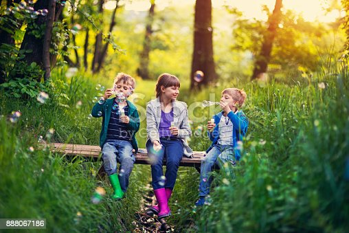 istock Three kids sitting on little bridge and blowing bubbles 888067186