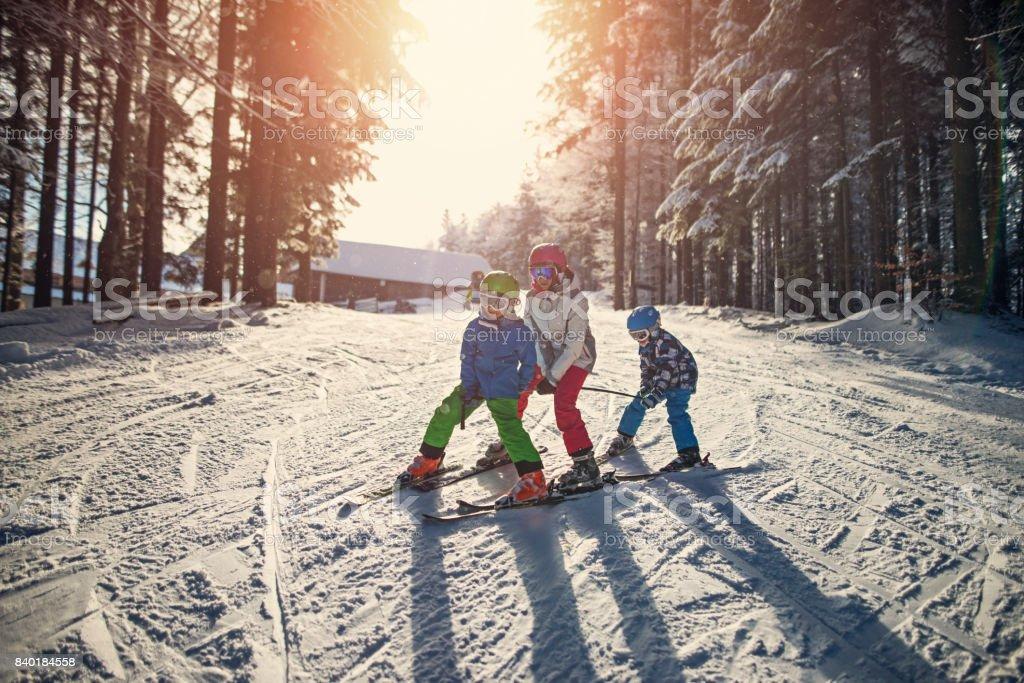 Three kids skiing on a beautiful winter day stock photo
