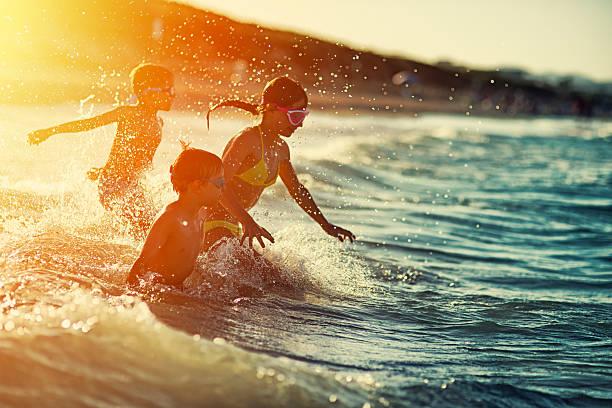 Three kids swimming and having fun at sea at sunset stock photo