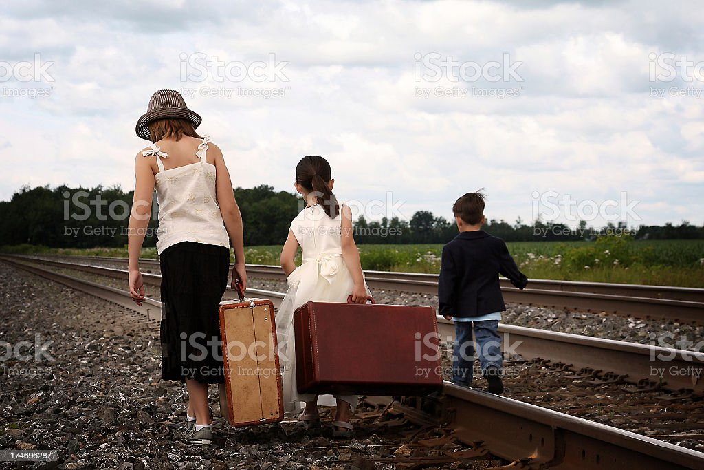 Three young children waiting for the train on a railway track. The...