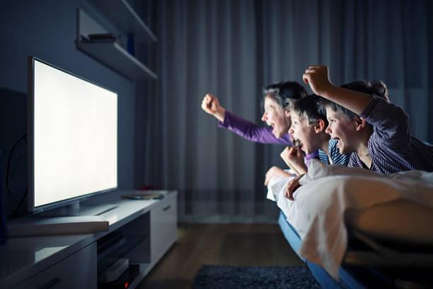 tres niños viendo la televisión y animando - family watching tv fotografías e imágenes de stock