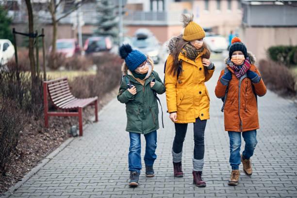 Drei Kinder mit Anti-Virus-Masken gehen zur Schule – Foto