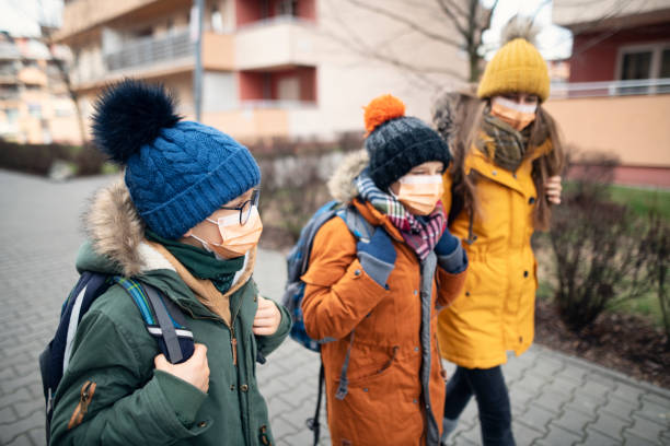 Three kids wearing anti virus masks going to school Three kids wearing anti virus masks. Kids are going to school.  Shot with BMPCC4k with Q0 Raw pollution mask stock pictures, royalty-free photos & images
