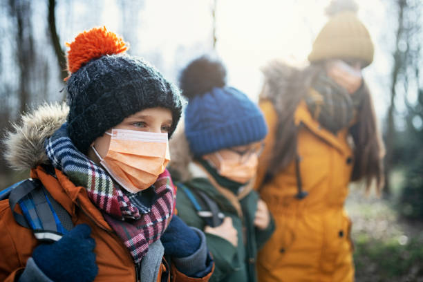 three kids wearing anti virus masks going to school - polmonite virus foto e immagini stock