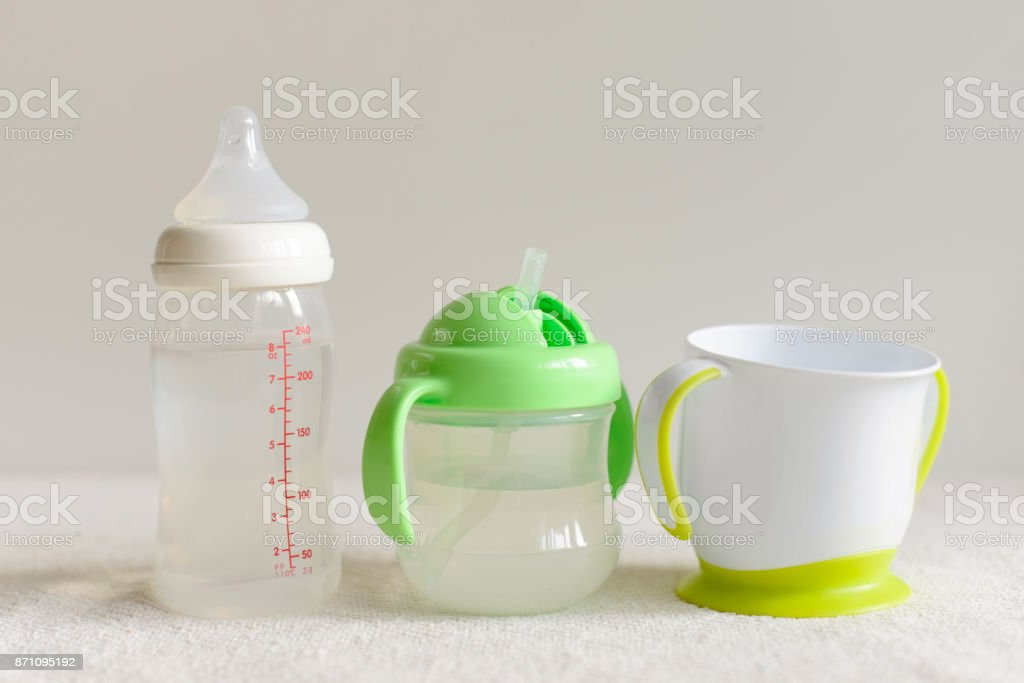 Three kinds of bottles and cups with water for baby. stock photo