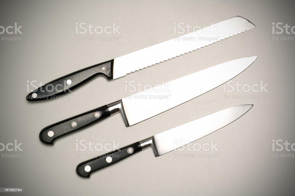 Three kitchen knifes on grey background royalty-free stock photo