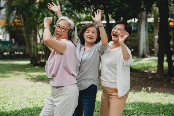 Three ladies listening to music and dancing together at the park stock photo