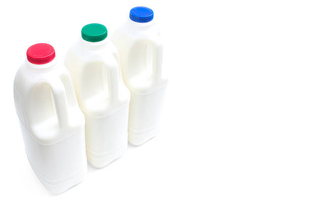 Three large bottles of milk on a white with path stock photo