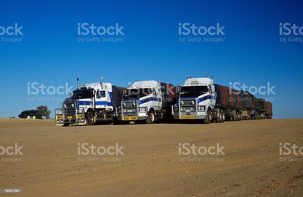 Three large trucks in the desert royalty-free stock photo