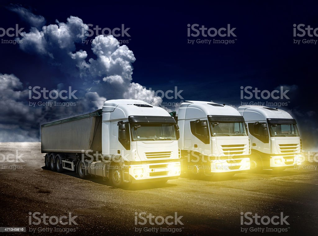 Three large trucks parked under the open sky stock photo