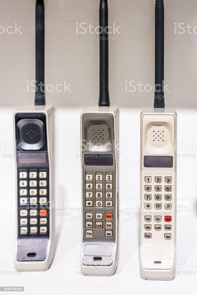 Três grandes vertical vintage portáteis celulares desatualizados telefones antigos permanente no visor com botões - foto de acervo