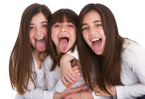 three latin american sisters sticking out tongues - sticking out tongue stock photos and pictures