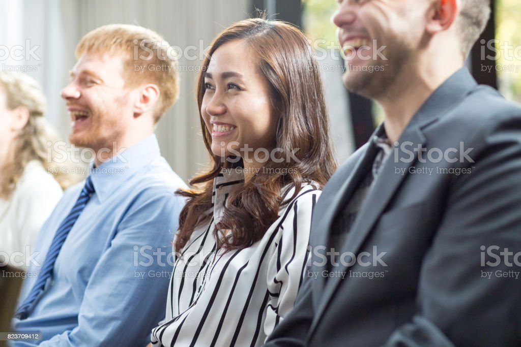 Closeup of three smiling adult business people sitting at lecture....
