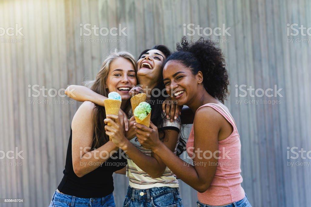 Trois amies qui rieurs avec crème glacée permanent à l'extérieur ensemble - Photo