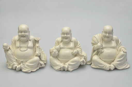 close up of three laughing white buddhas isolated on white background