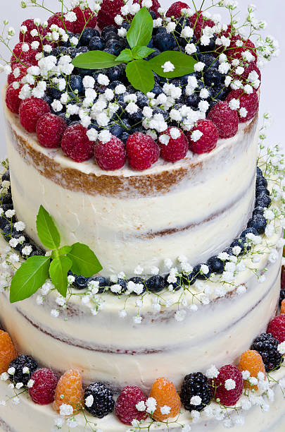 three layered wedding cake with berries and basil leaves stock photo