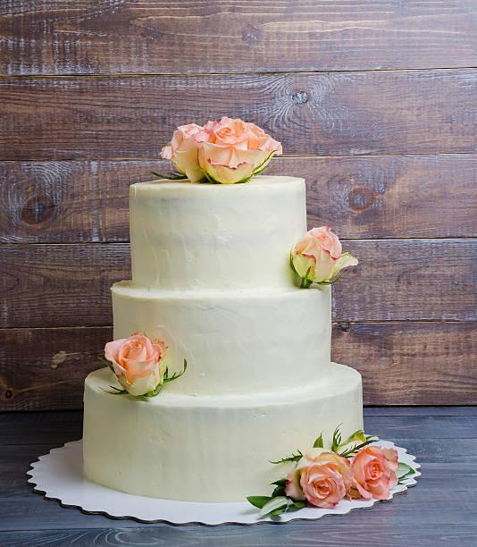 three layered wedding cake with roses stock photo