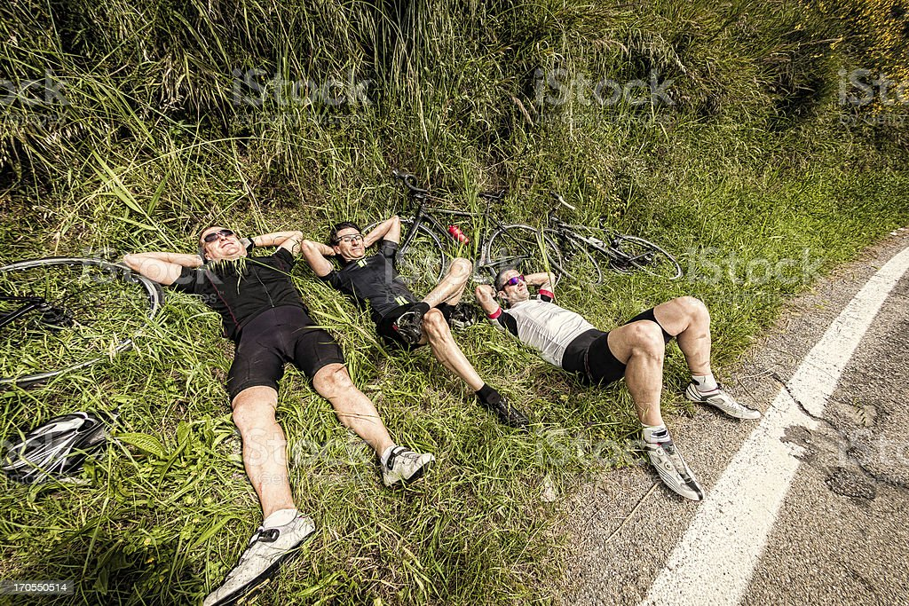Three Lazy Cyclists Resting on Side of the Road stock photo