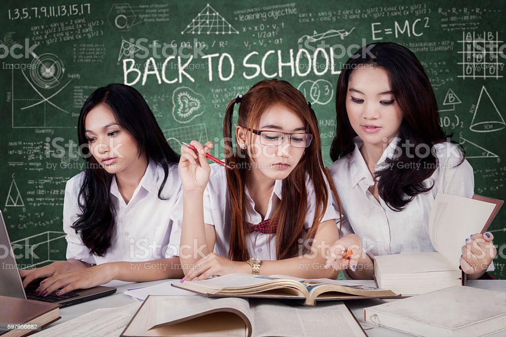 Three learners doing assignment together stock photo