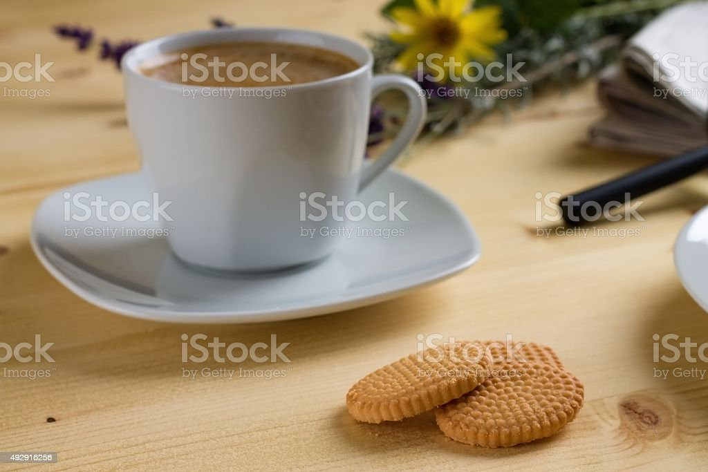 Three lemon biscuits in front of coffee stock photo