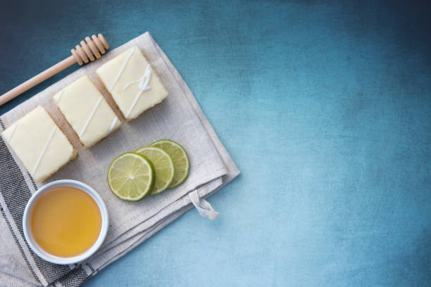 drei zitronen-kuchen mit limettenscheiben und einen topf honig - 3 zutaten kuchen stock-fotos und bilder