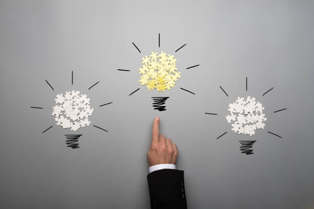 Three light bulbs made of scattered white and yellow puzzle pieces with a hand of a businessman stock photo