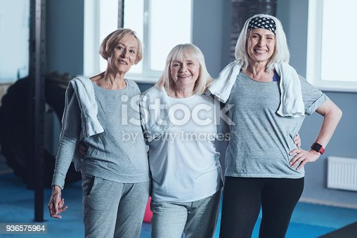 936573360 istock photo Three likeminded sporty elderly ladies posing at fitness club 936575964