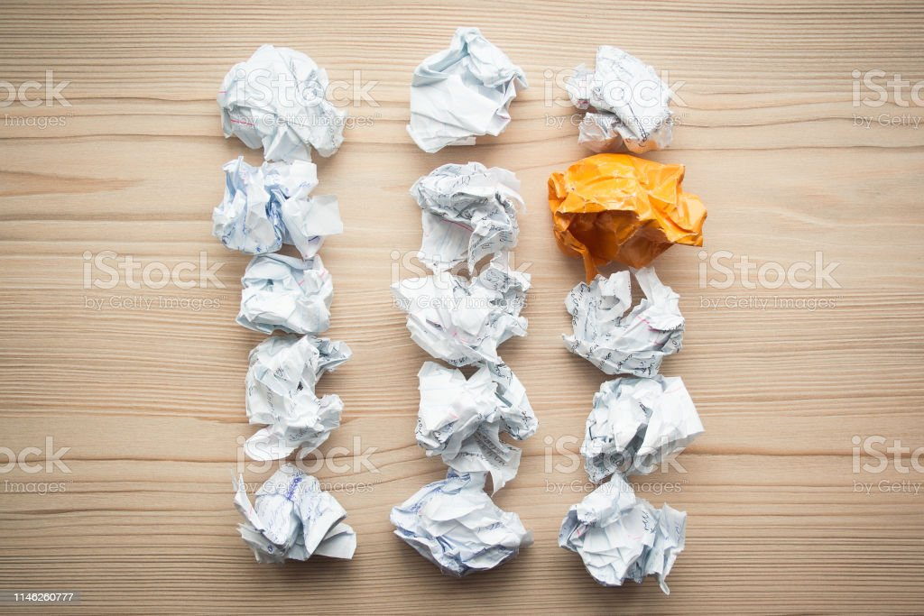 Three lines of crumpled white paper balls with one different orange...