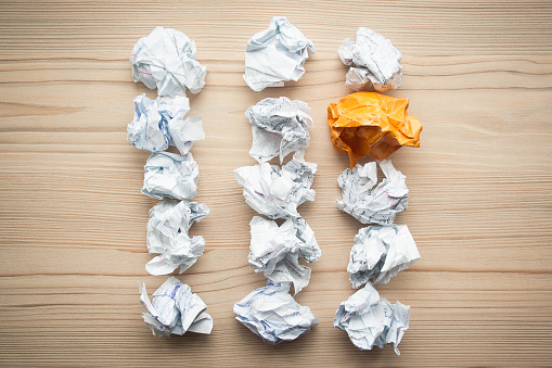 istock Three lines of crumpled white paper balls with one different orange paper ball between them. Concept of think different, think out of the box, leadership. 1146260777