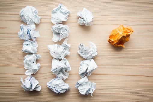 istock Three lines of crumpled white paper balls with one different orange paper ball between them. Concept of think different, think out of the box, leadership. 1146260809